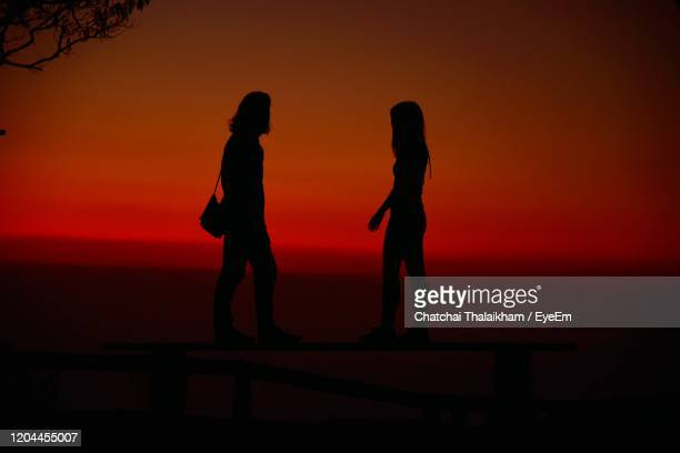 silhouette people standing against sea during sunset - chatchai thalaikham stock pictures, royalty-free photos & images