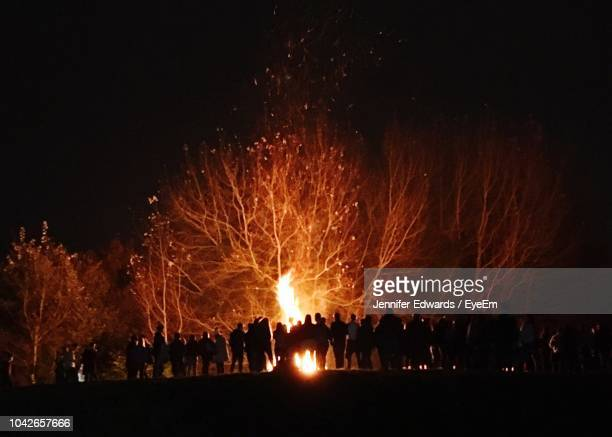 silhouette people standing around bonfire at night - burns night stock pictures, royalty-free photos & images