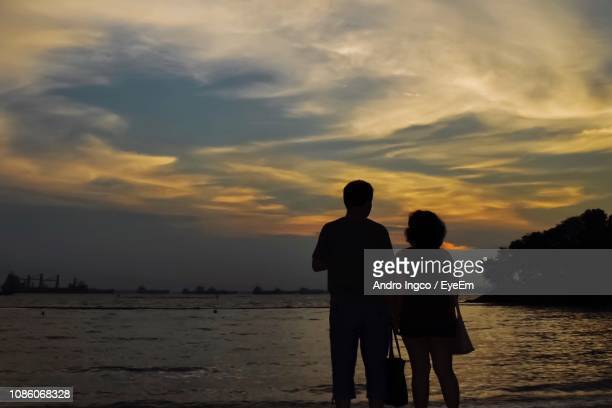 Silhouette People Standing At Beach Against Sky During Sunset