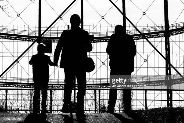 Silhouette People Standing By Fence