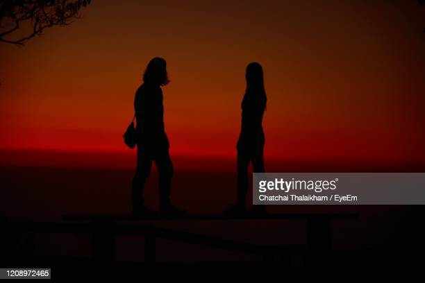 silhouette people standing by sea against sky during sunset - chatchai thalaikham stock pictures, royalty-free photos & images
