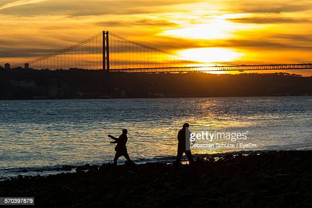 Silhouette People Standing By Sea With Ponte 25 De Abril Bridge Against Sunset Sky