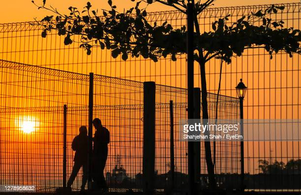 silhouette people standing by tree against orange sky - prison stock pictures, royalty-free photos & images
