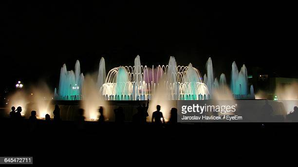 Silhouette People Standing In Front Of Magic Fountain At Night