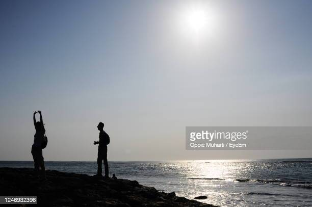 silhouette people standing on beach against clear sky - oppie muharti stock pictures, royalty-free photos & images