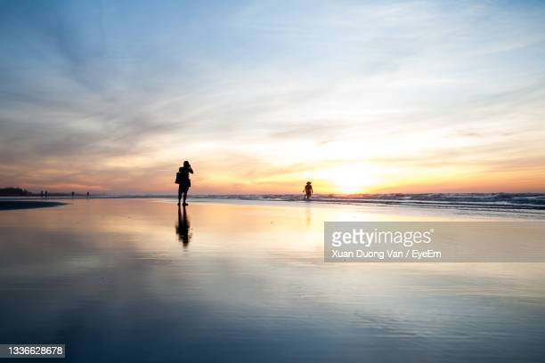 silhouette people standing on beach against sky during sunset - ナムディン ストックフォトと画像