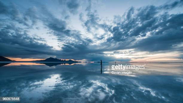 silhouette people standing on bonneville salt flats against cloudy sky - bonneville salt flats stock pictures, royalty-free photos & images