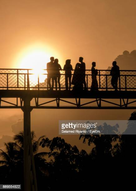 Silhouette People Standing On Bridge Against Clear Sky During Sunset