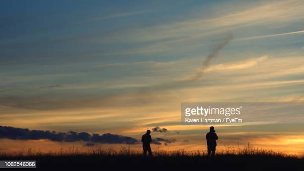 silhouette people standing on field against sky during sunset - coral springs stock pictures, royalty-free photos & images