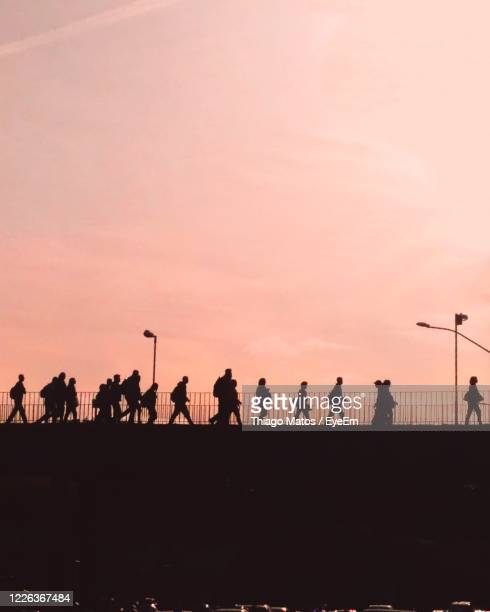 silhouette people standing on field against sky during sunset - belo horizonte stock pictures, royalty-free photos & images