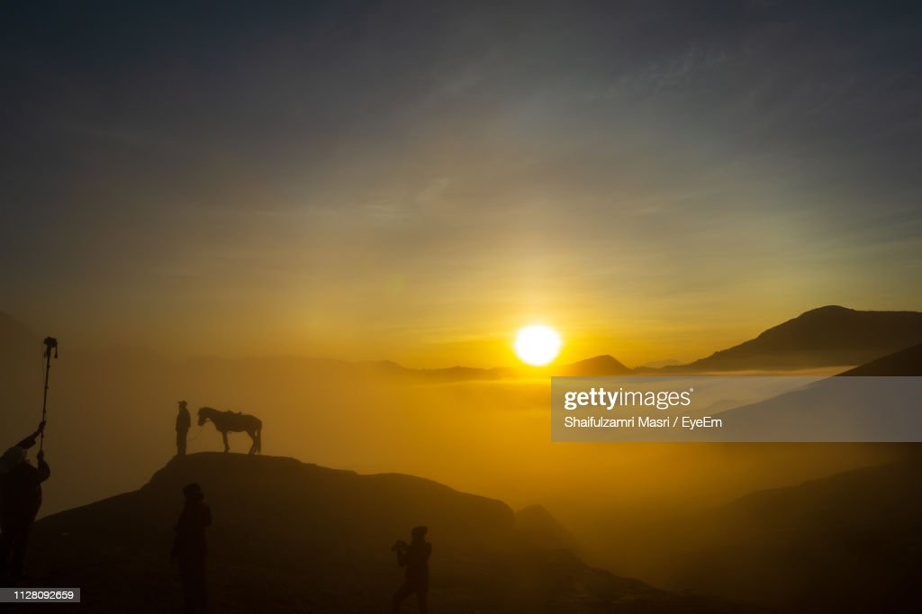 Silhouette People Standing On Mountains Against Sky During Sunset : Stock Photo