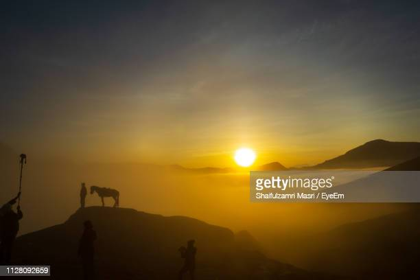 Silhouette People Standing On Mountains Against Sky During Sunset
