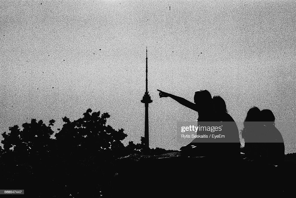 Silhouette People Standing On Retaining Wall Looking At Tower Against Sky : Stock Photo