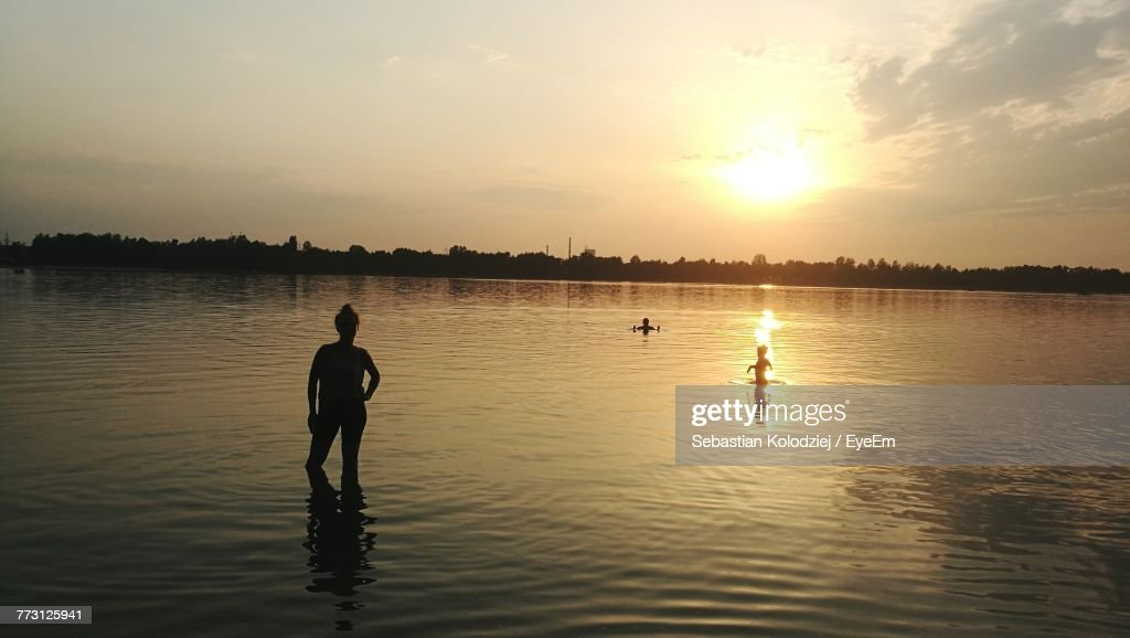 Silhouette People Swimming In Lake Against Sky During Sunset : Stock Photo