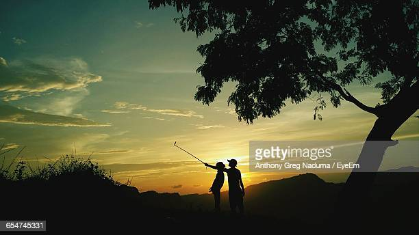 silhouette people taking selfie by tree against sky during sunset - bugo foto e immagini stock
