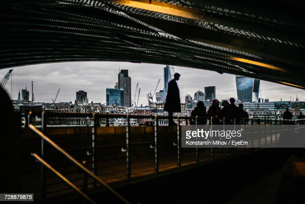 Silhouette People Under Bridge Against Cityscape