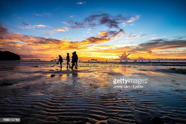 silhouette people walking at beach against sky during sunset - sarawak state stock pictures, royalty-free photos & images