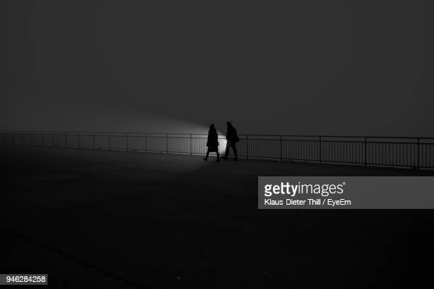 Silhouette People Walking On Bridge Against Clear Sky