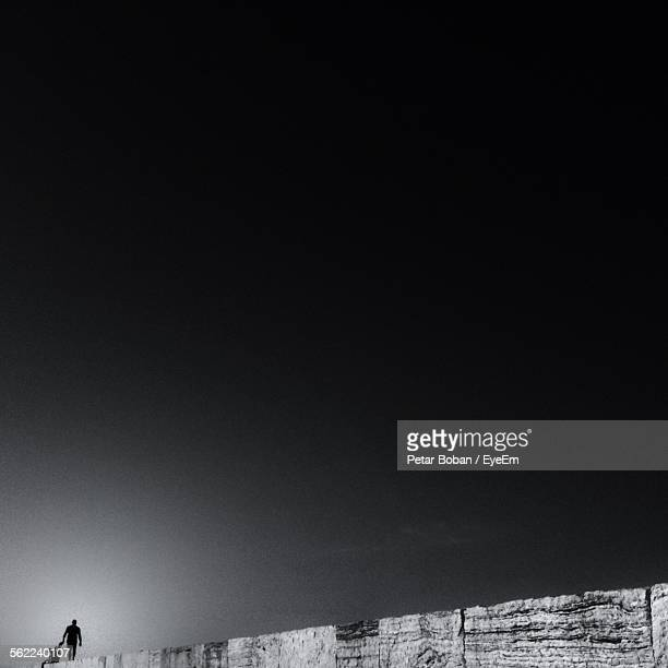 silhouette people walking on concrete wall against gray sky at rovenska beach - boban stock pictures, royalty-free photos & images