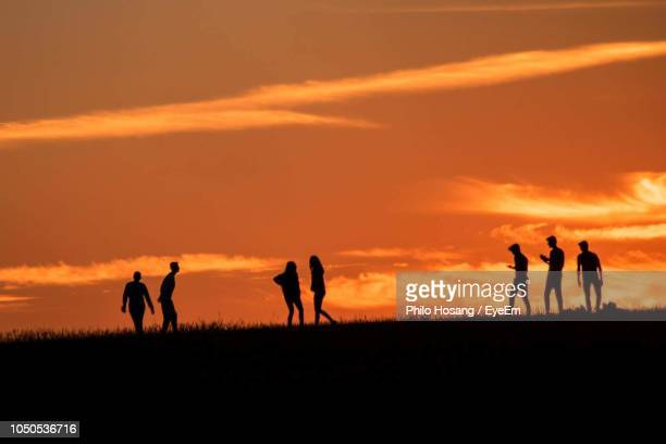 silhouette people walking on field against sky during sunset - groupe moyen de personnes photos et images de collection