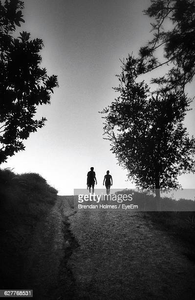 silhouette people walking on road against clear sky - middlebare afstand stockfoto's en -beelden
