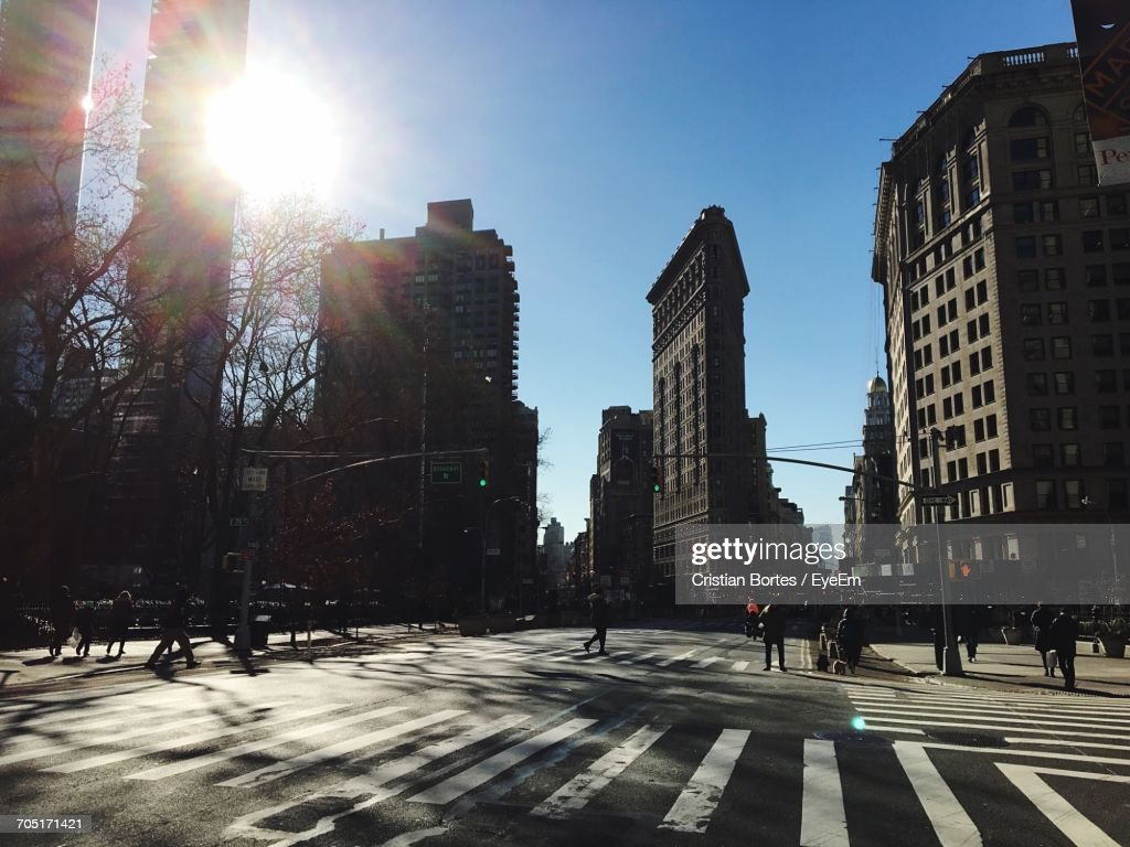 Silhouette People Walking On Street By Buildings In City Against Blue Sky During Sunny Day