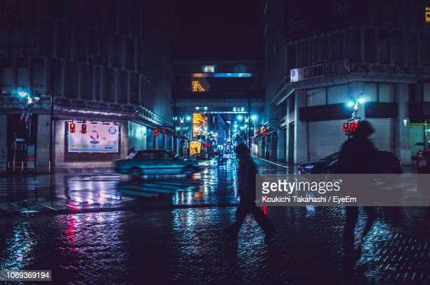 Silhouette People Walking On Wet Street In Illuminated City