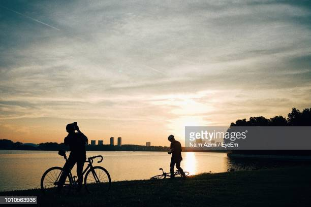 silhouette people with bicycles at lakeshore against sky during sunset - putrajaya stock photos and pictures