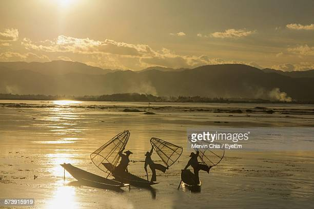Silhouette People With Fishing Net On Boat In Lake During Sunset
