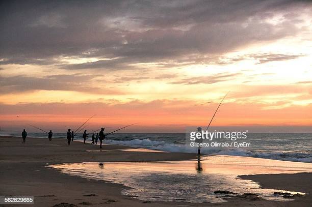 Silhouette People With Fishing Rods On Beach Against Orange Sky