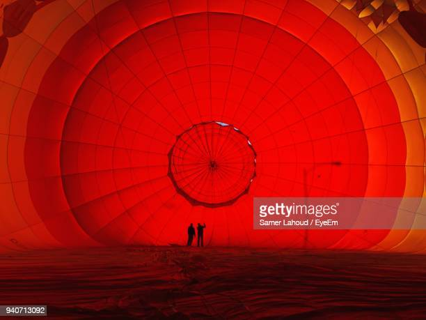 silhouette people with hot air balloon at desert - comparison stock photos and pictures