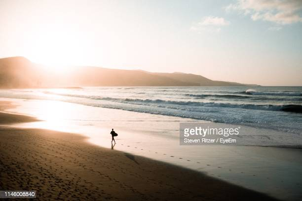 silhouette person at beach against sky during sunset - grand canary stock pictures, royalty-free photos & images