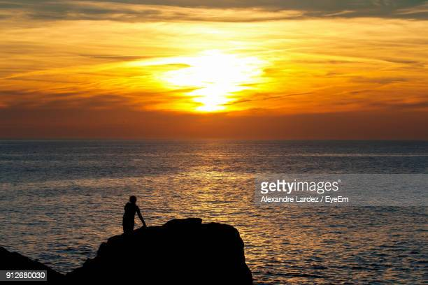 Silhouette Person At Beach Against Sky During Sunset