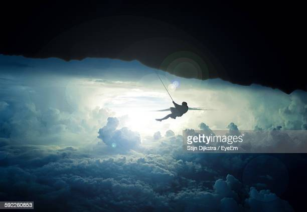 Silhouette Person Climbing On Mountain Over Cloudy Sky