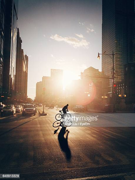 silhouette person cycling on street during sunset - radfahren stock-fotos und bilder