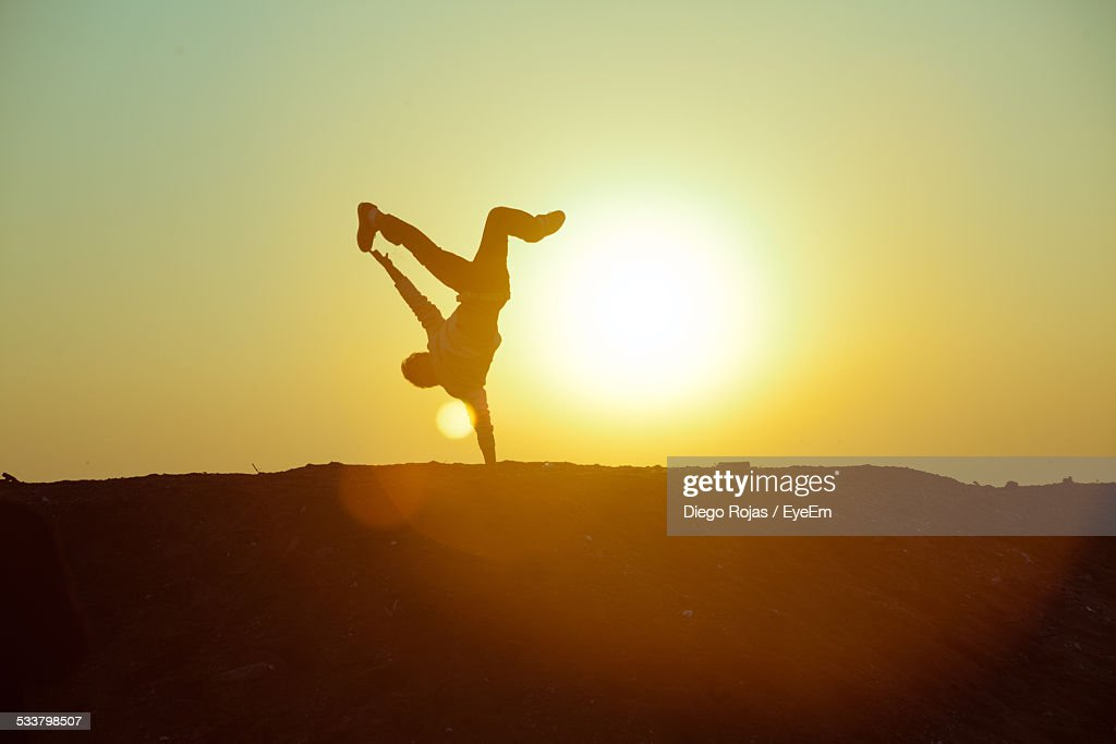 Silhouette Person Doing Handstand Against Sky During Sunset : Foto stock