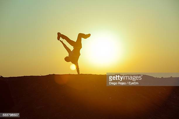 Silhouette Person Doing Handstand Against Sky During Sunset
