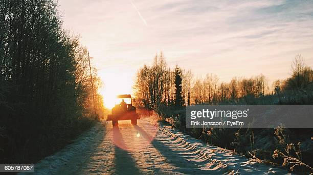 Silhouette Person Driving Tractor On Dirt Road Against Sky During Sunset
