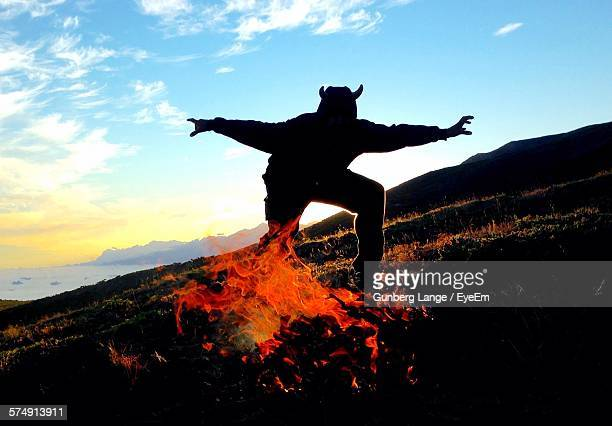 silhouette person in devil costume dancing by campfire on hill - devil costume stockfoto's en -beelden