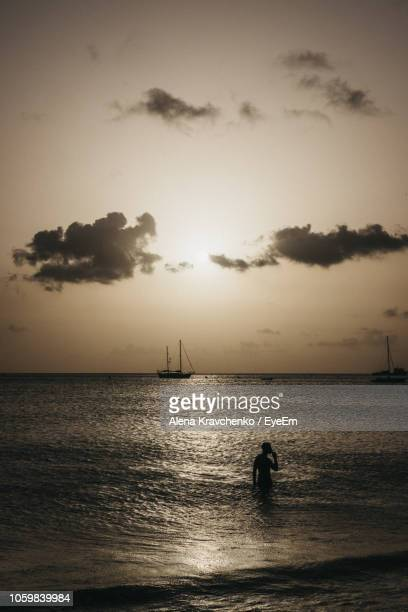 silhouette person in sea against sky at dusk - bridgetown barbados stock pictures, royalty-free photos & images