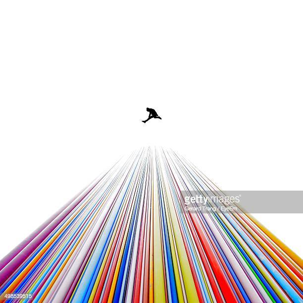 Silhouette person jumping over colorful mount against white background