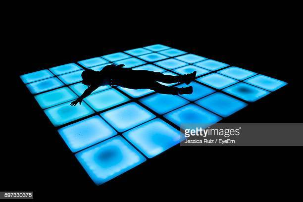 Silhouette Person Lying On Blue Dance Floor At Nightclub