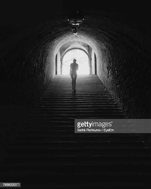 silhouette person moving up steps in tunnel - ウクライナ トンネル ストックフォトと画像