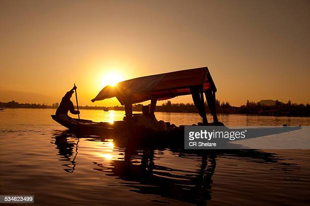 Silhouette person rowing a boat