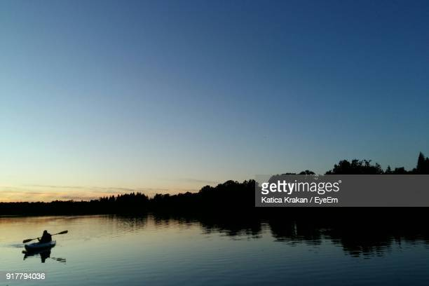 Silhouette Person Sailing Boat In Lake Against sky