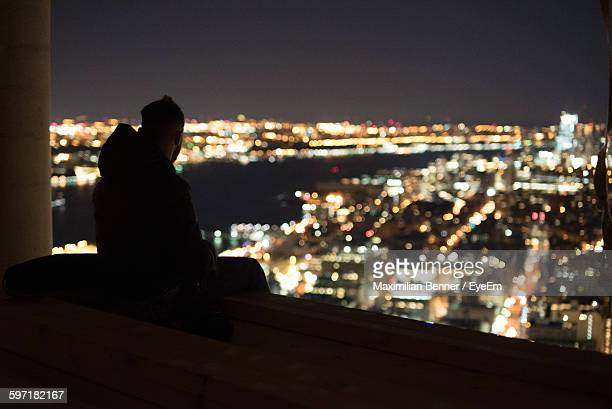 Silhouette Person Sitting At Window Against Illuminated Cityscape At Night