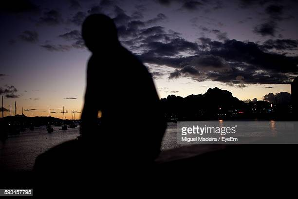silhouette person sitting by lake against sky during sunset - cabo verde imagens e fotografias de stock