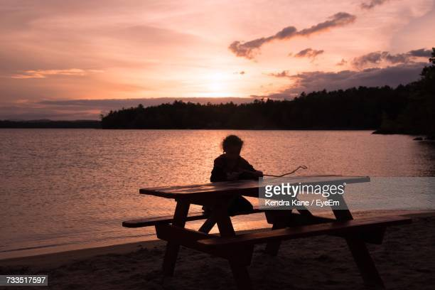 silhouette person sitting on beach against sky during sunset - lake solitude (new hampshire) stock photos and pictures