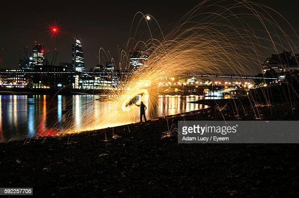 Silhouette Person Spinning Wire Wool By River In City At Night