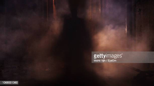 silhouette person standing amidst smoke at night - ghost stock pictures, royalty-free photos & images